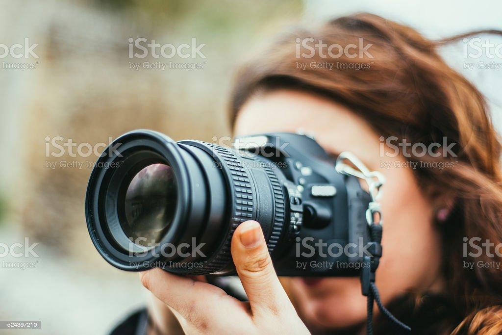 Młoda kobieta za pomocą DSLR kamery – zdjęcie