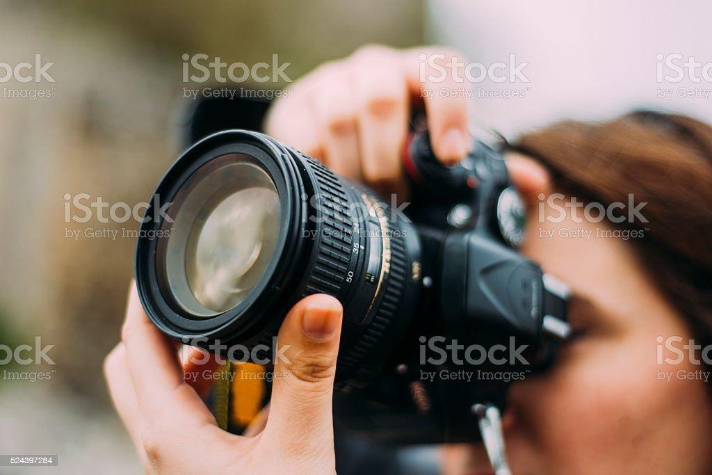 若い女性交換できるデジタル一眼レフカメラを使用 - 1人のロイヤリティフリーストックフォト