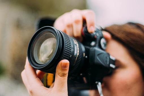 若い女性交換できるデジタル一眼レフカメラを使用 - 1人のストックフォトや画像を多数ご用意