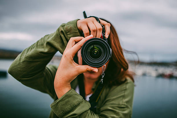 junge frau mit dslr-kamera - fotografische themen stock-fotos und bilder
