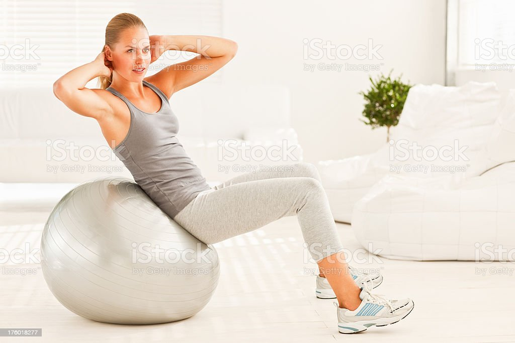 Young woman using exercise ball to workout royalty-free stock photo