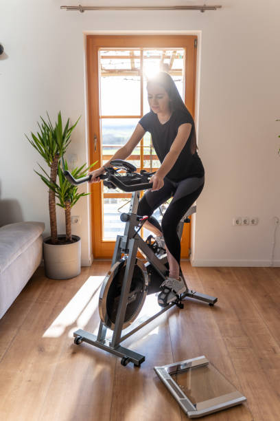 Young woman using exercise bike at home stock photo