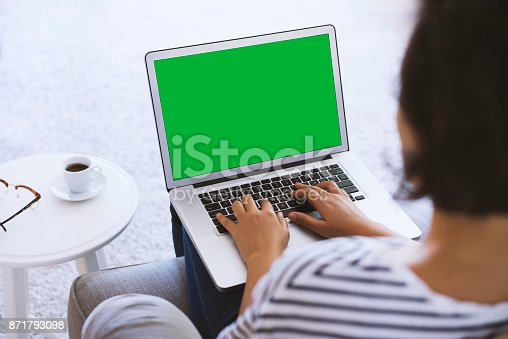istock Young woman using green screen laptop 871793098