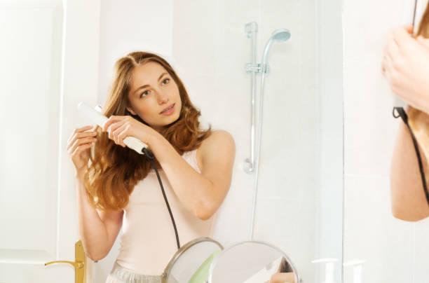 junge frau mit haarglätter im badezimmer - badezimmer new york style stock-fotos und bilder