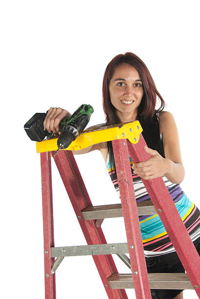 Young woman using hand dril tool and step ladder stock photo