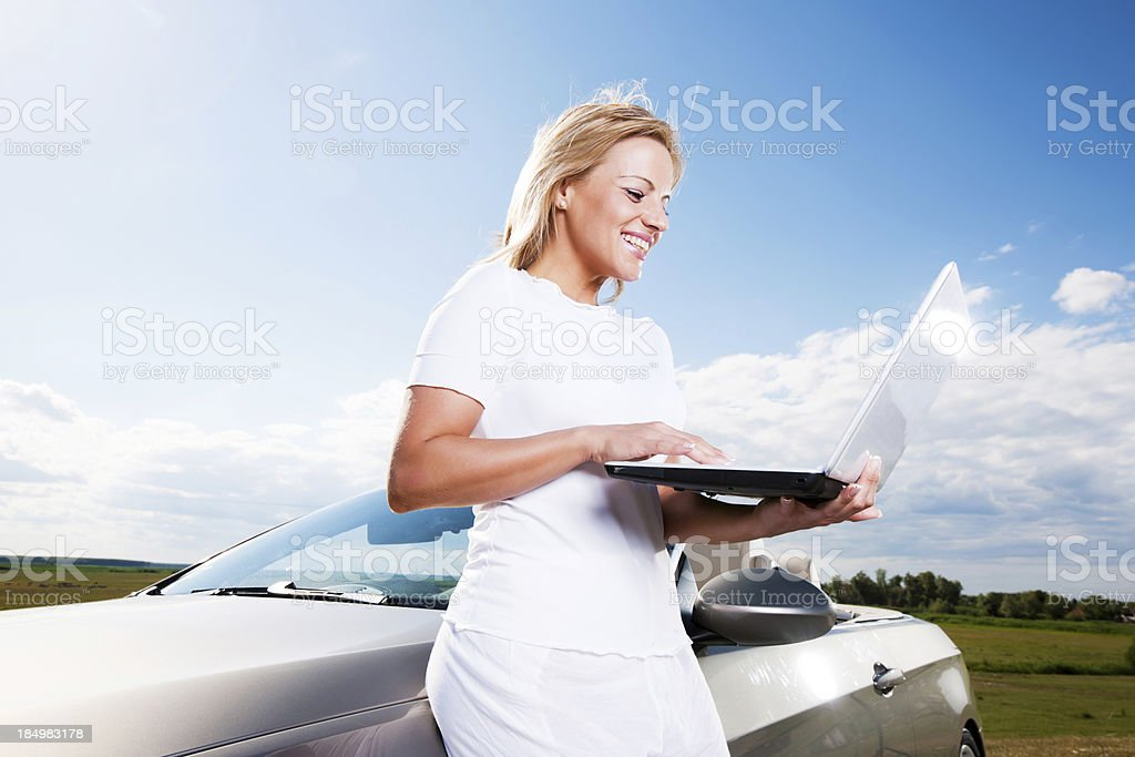 Young woman using her laptop against the sky and clouds. royalty-free stock photo