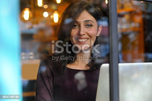 Smiling young girl seen through window of a modern coffee shop, working at laptop computer