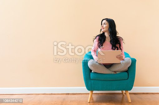 Young woman using her laptop on a blue chair