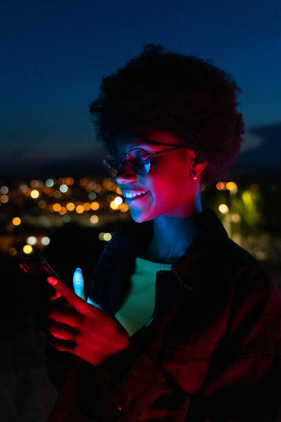 Young woman using her mobile phone at night with the city at background stock photo