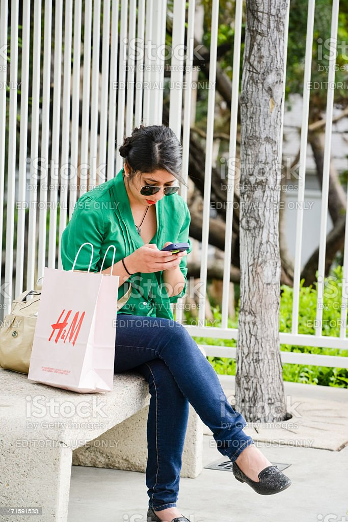 Young woman using her mobile phone outdoors royalty-free stock photo