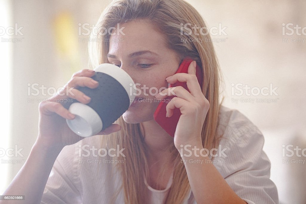 Young woman using her smart phone at home in the morning stock photo