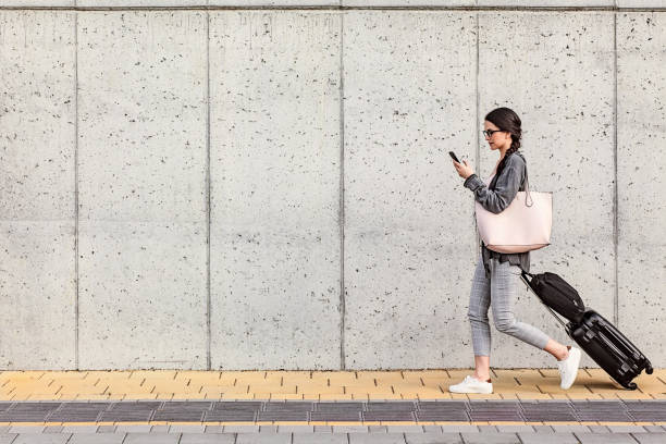 Young woman using her smart phone walking beside the concrete wall and pulling a small wheeled luggage with a briefcase on it stock photo