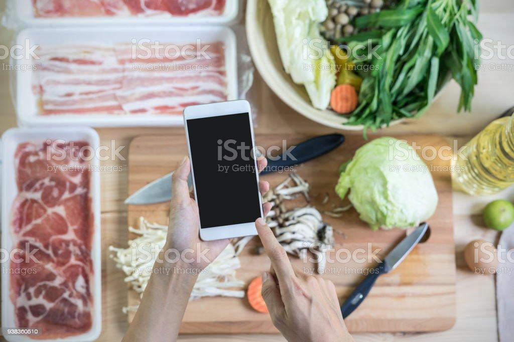 Junge Frau mit ihrem Smartphone in der Küche – Foto