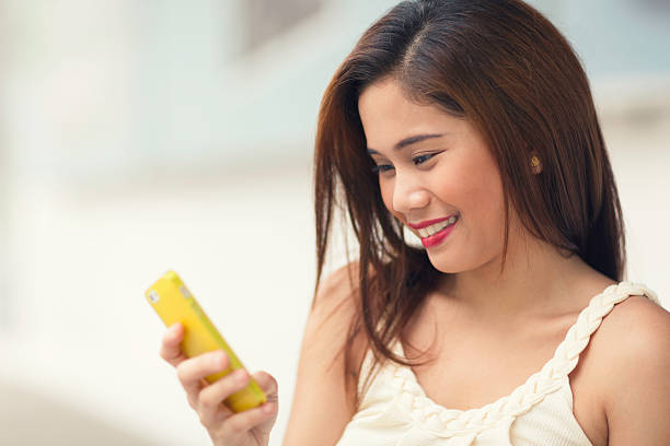 Young woman using her smartphone A young woman outdoors smiling, using or dialing on her smartphone. filipino ethnicity stock pictures, royalty-free photos & images