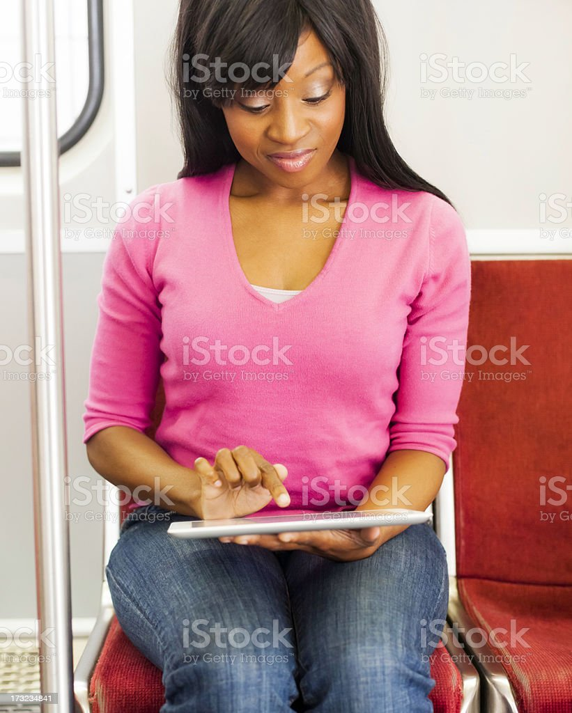 Young Woman Using her Tablet on the Subway royalty-free stock photo