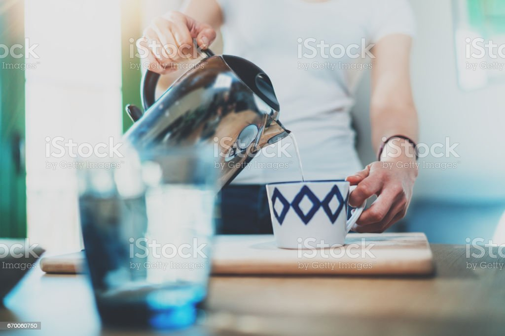 Young woman using kettle for make tea or black coffee on kitchen at room interior background.Women's hands pour water from a teapot into a cup. Blurred, flares effect. stock photo