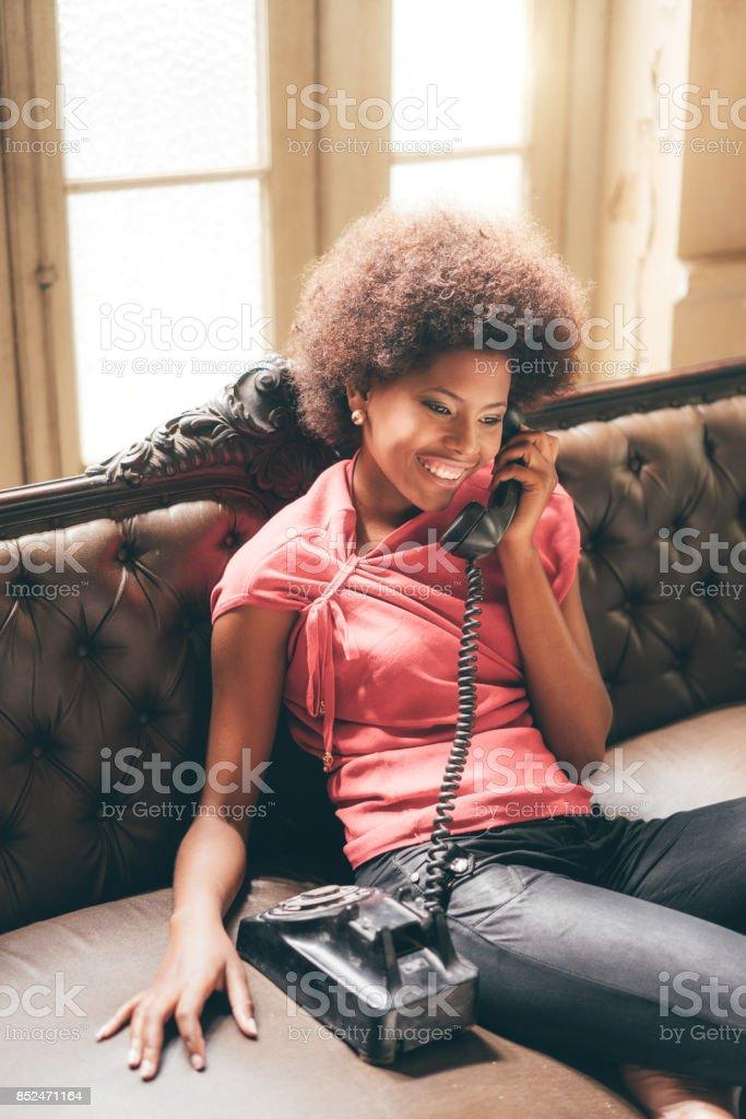 young woman using landline telephone stock photo