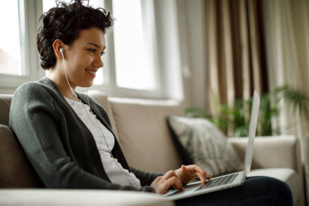 Young woman using laptop and listening to music at home stock photo