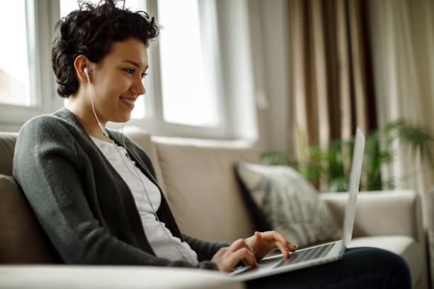 Junge Frau mit Laptop und Musikhören zu Hause – Foto
