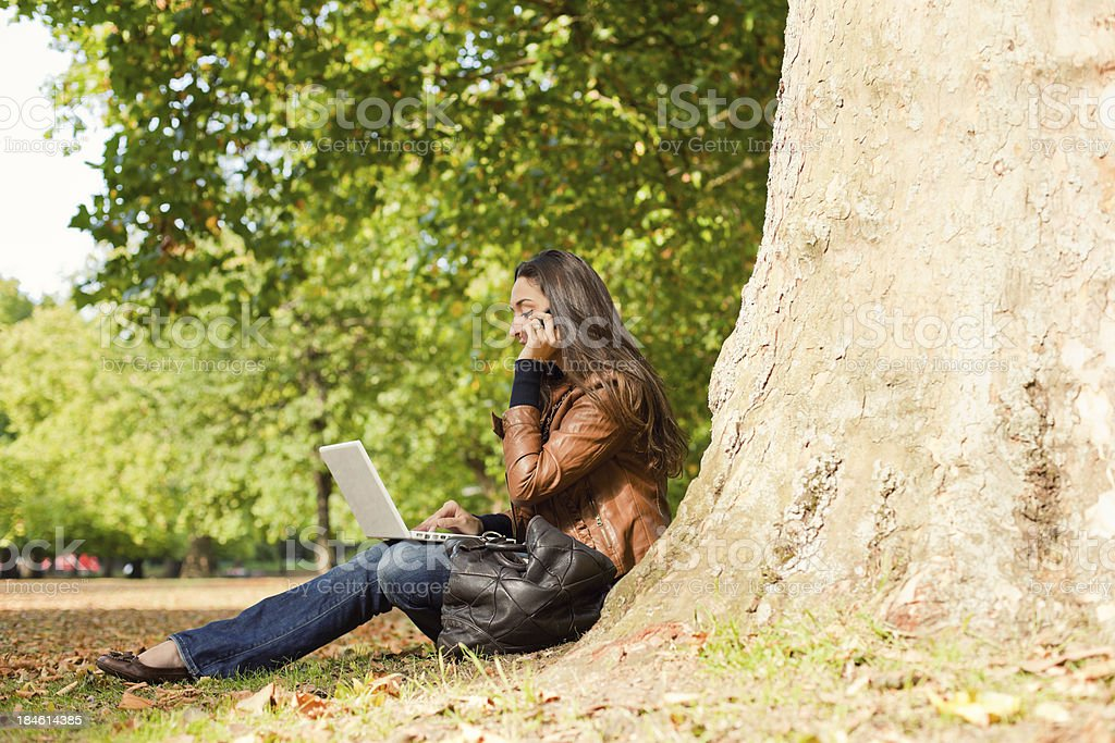 Young Woman Using Laptop and Phone in a Park royalty-free stock photo