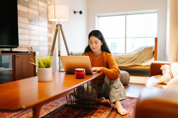 young woman using laptop comfortably at home - ásia imagens e fotografias de stock