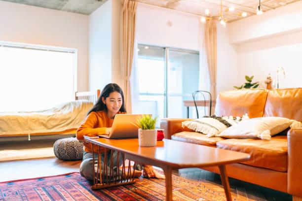 自宅で快適にラップトップを使用して若い女性 - people of color ストックフォトと画像