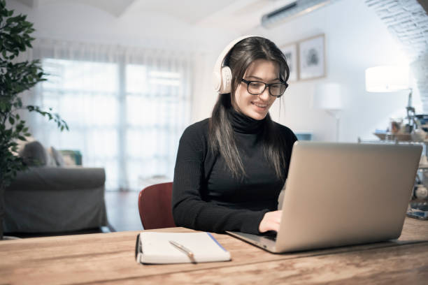 Young woman using laptop computer at home stock photo