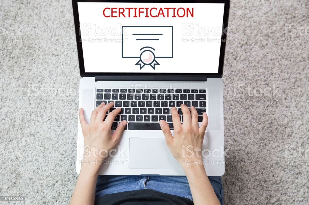 Young woman using laptop computer . CERTIFICATION CONCEPT stock photo