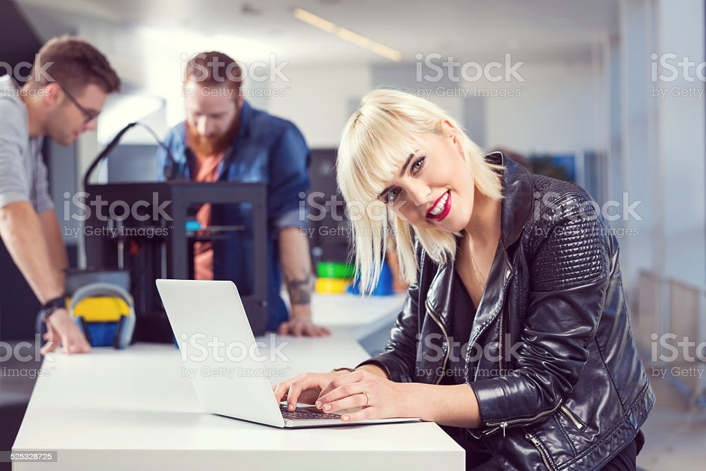 Young woman using laptop in 3D printer office Start-up Business. Young woman working on laptop in the office while her coworkers using 3D printer. 3D Printing Stock Photo