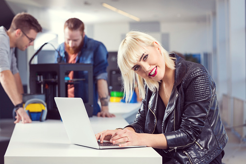 Young Woman Using Laptop In 3d Printer Office Stock Photo - Download Image Now