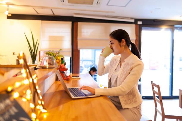 カフェでノート パソコンを使用しての若い女性 - フリーランス ストックフォトと画像
