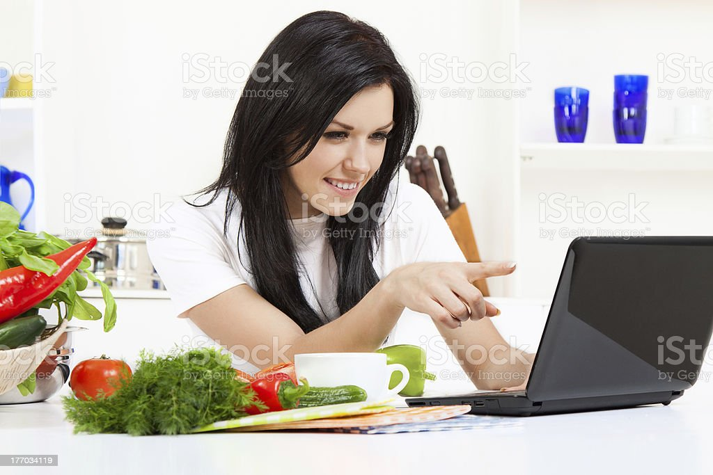 Young woman using laptop in kitchen royalty-free stock photo