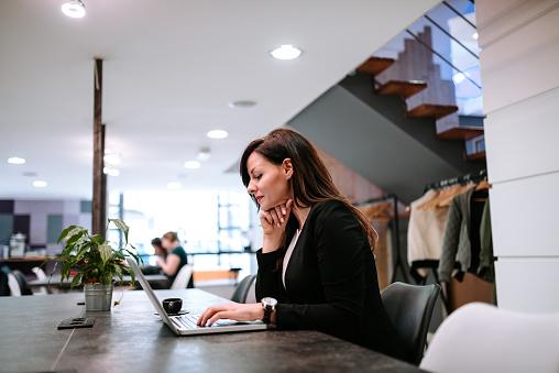 Foto de Jovem Mulher Usando Laptop No Escritório De Coworking Aberto e mais fotos de stock de Aberto
