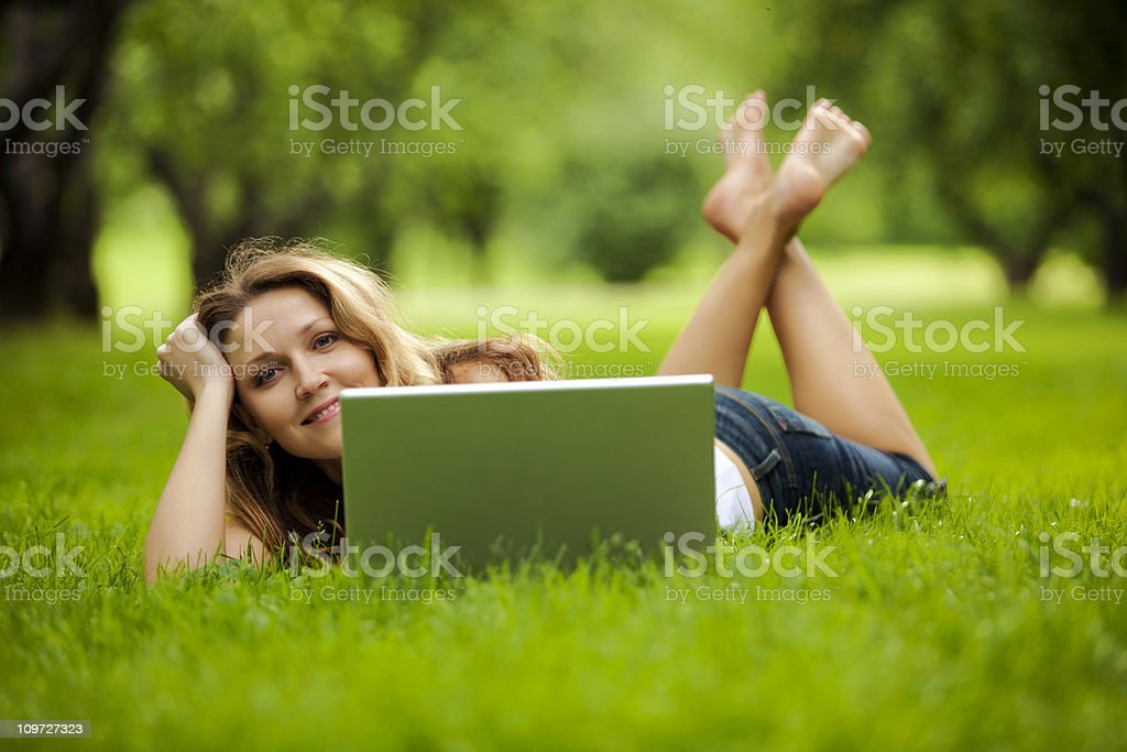 Young woman using laptop in park royalty-free stock photo