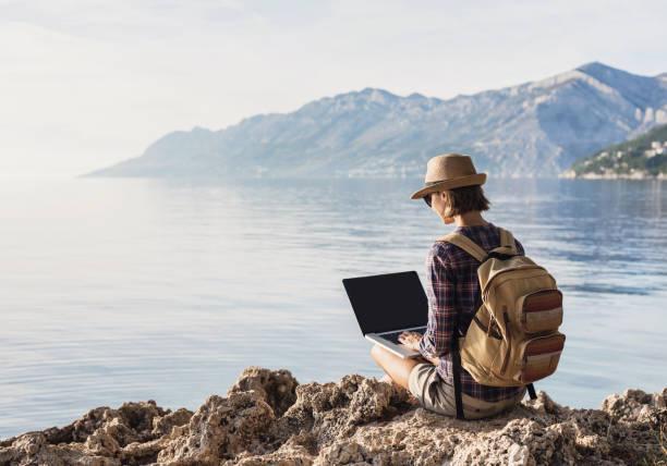 junge frau mit laptop in der nähe des meeres - reiseblogger stock-fotos und bilder