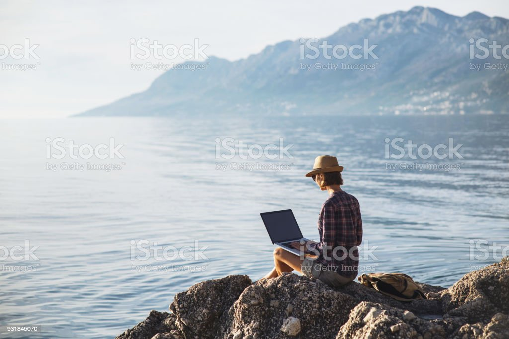 Young woman using laptop near the sea stock photo