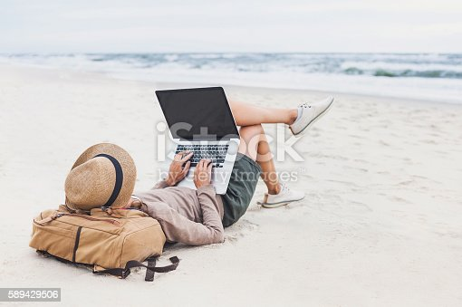 istock Young woman using laptop on a beach 589429506