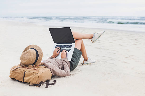 young woman using laptop on a beach - tagesrechner stock-fotos und bilder