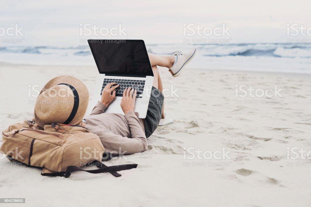Joven mujer utilizando la computadora portátil en una playa - foto de stock