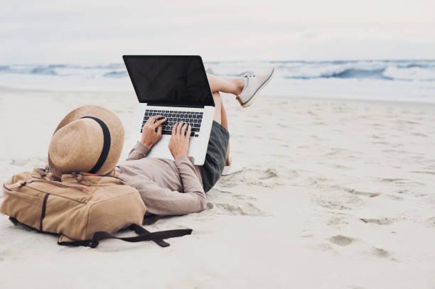 junge frau mit laptop am strand - reiseblogger stock-fotos und bilder