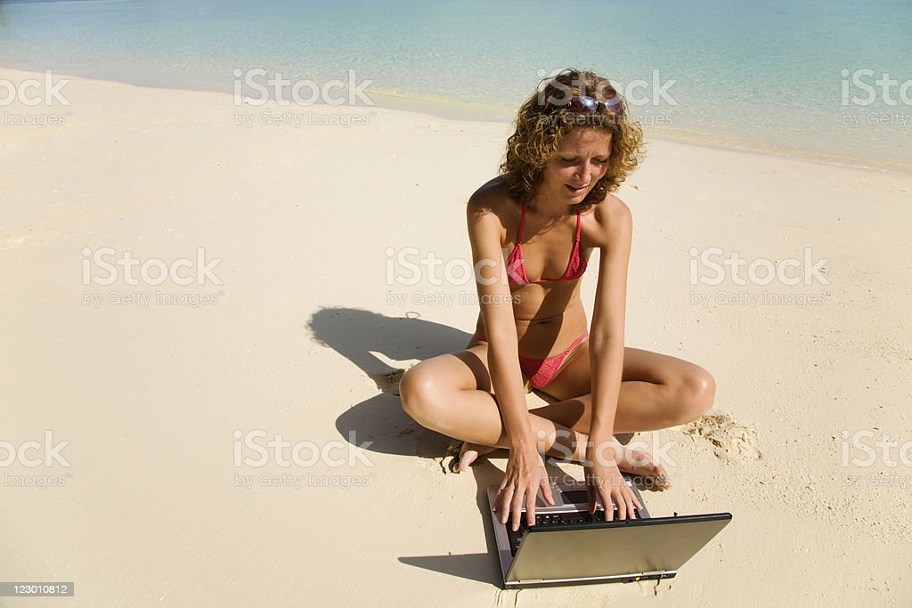 Young woman using laptop on beach royalty-free stock photo