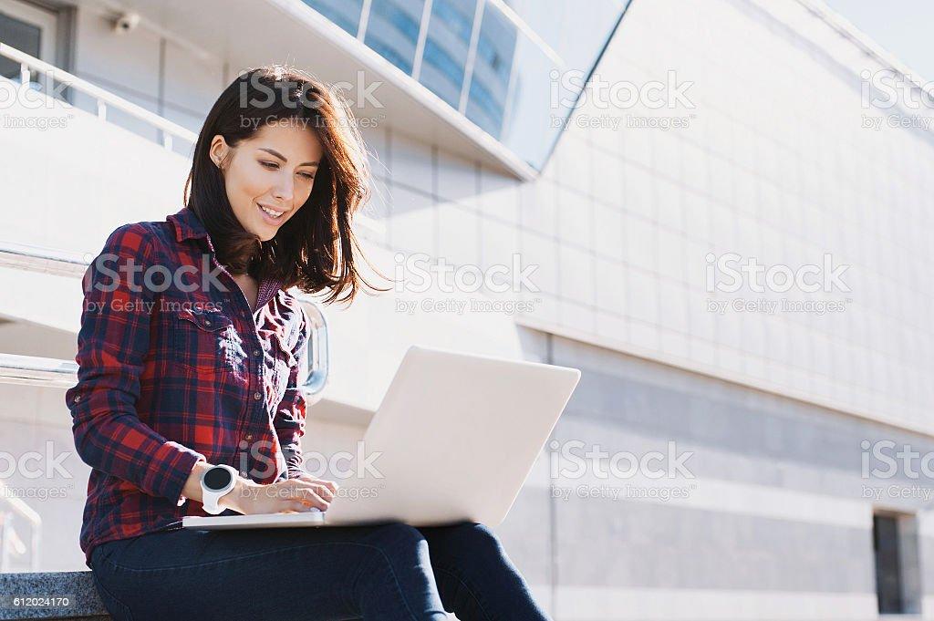 Jovem mulher usando um laptop ao ar livre - foto de acervo