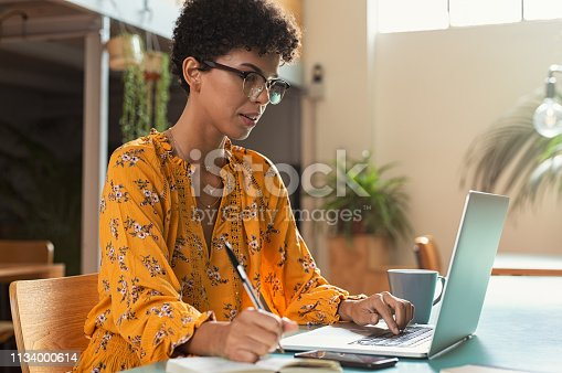 Focused college student sitting in cafeteria taking notes while using laptop. Young brazilian woman doing research for business at coffee shop. African american girl sitting in cafe using computer and writing notes.