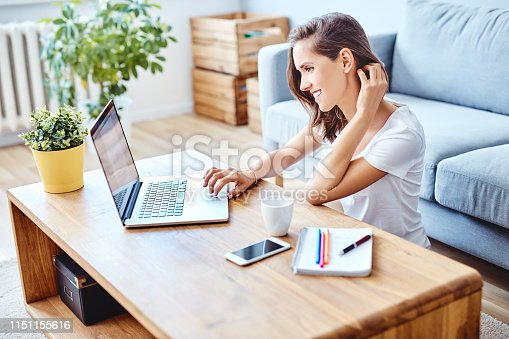 Young woman using laptop sitting on floor in living room at home