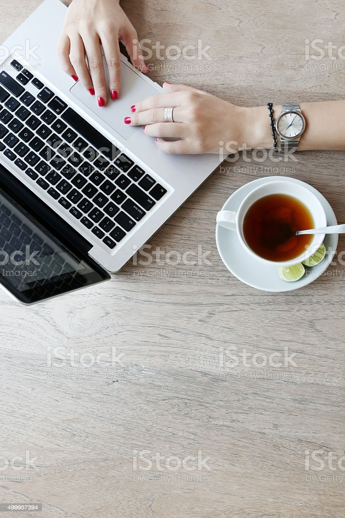 Young woman using laptop while drinking tea stock photo