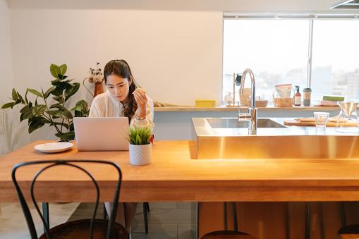 自宅で朝食をとりながらノートパソコンを使った若い女性 - 1人のストックフォトや画像を多数ご用意
