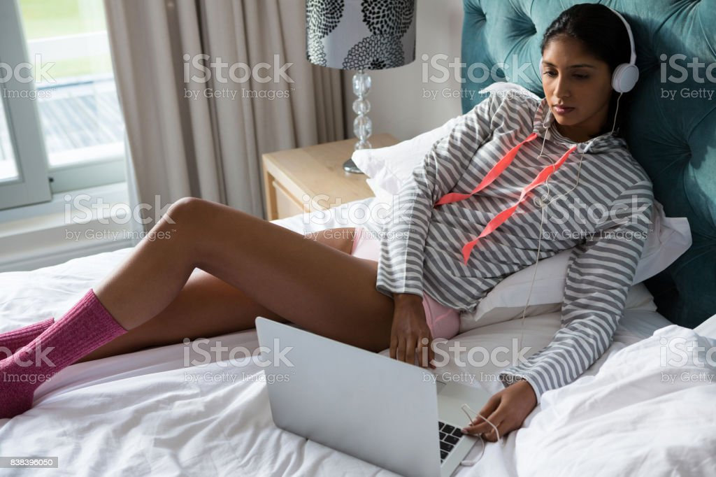 Young woman using laptop while listening to music on bed - Royalty-free 20-29 Years Stock Photo