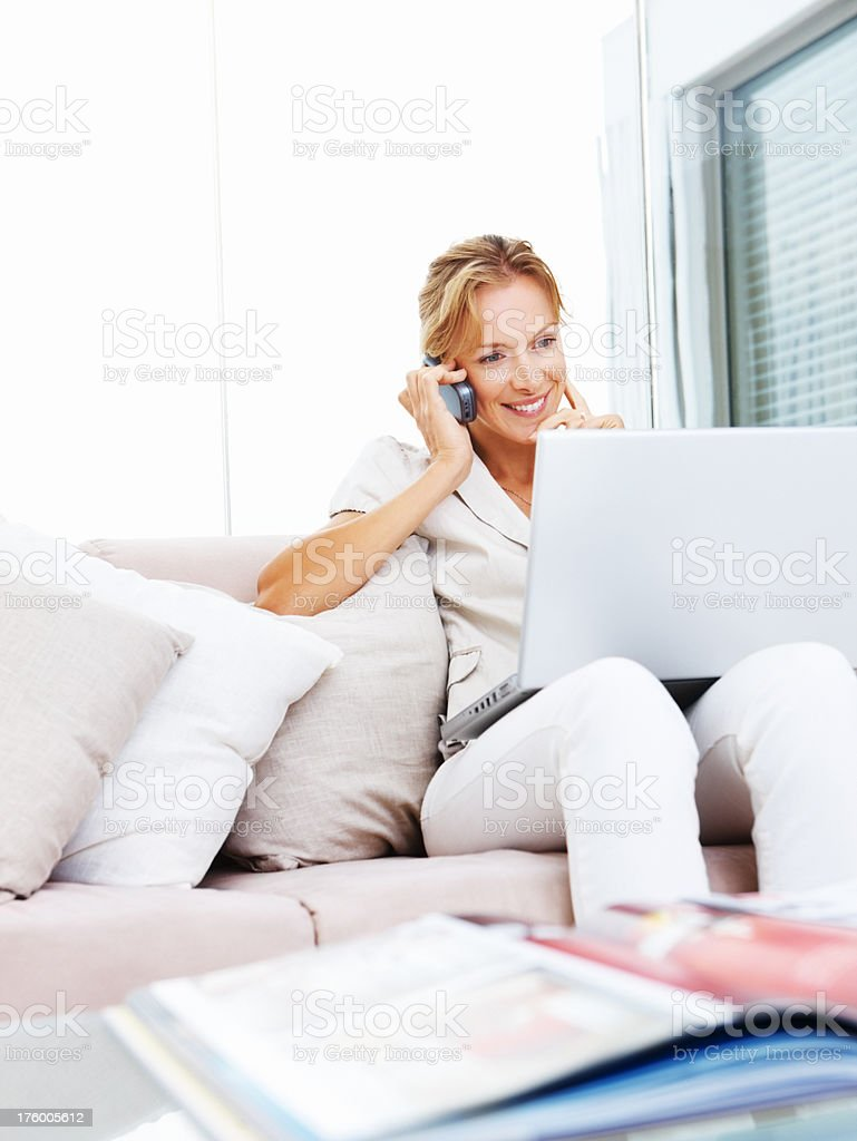 Young woman using laptop while speaking on cellphone royalty-free stock photo