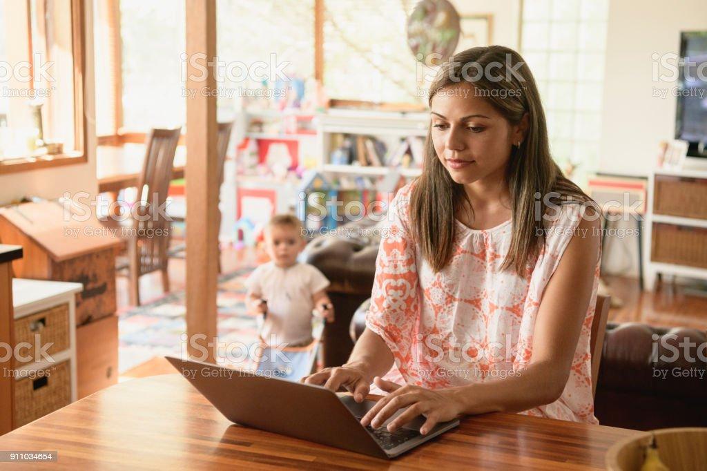 Junge Frau mit Laptop mit Baby Sohn im Hintergrund – Foto