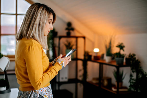 Young woman using mobile at her home stock photo